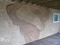 custom concrete wall with boulder extruding